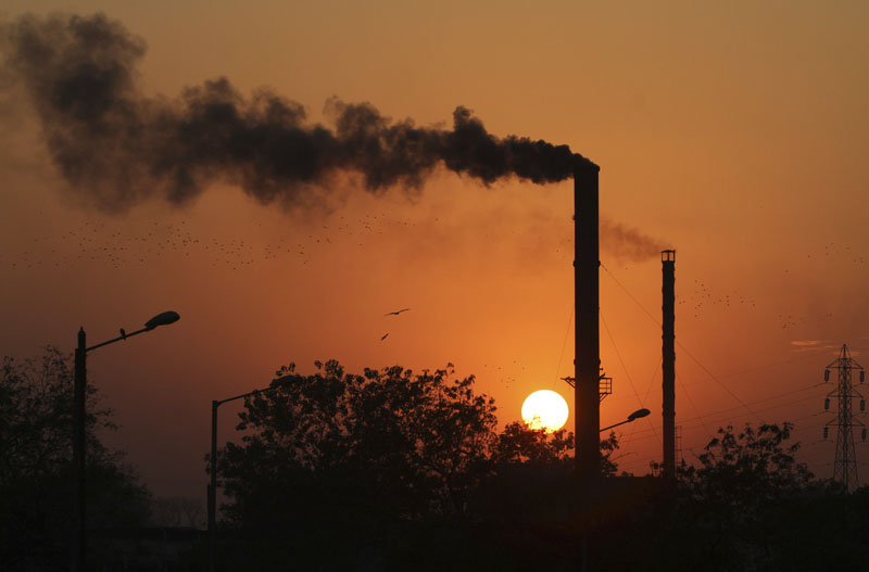 FILE - Birds as they fly past at sun set as smoke emits from a chimney at a factory in Ahmadabad, India, on Monday, December 8, 2014. Photo: Ajit Solankii/AP