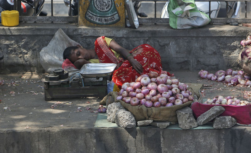 An Indian vendor selling onions on a sidewalk rests under the shade of a tree on a hot summer day in Hyderabad, India, on Wednesday, April 20, 2016. Photo: Mahesh Kumar A/AP