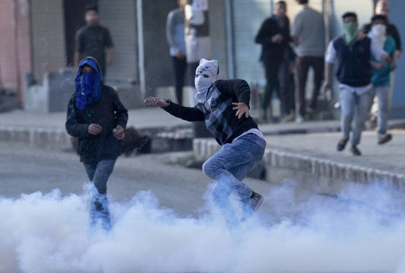 A Kashmiri masked Muslim protester throws rocks and bricks at Indian policemen amid tear gas smoke during a protest in Srinagar, Indian controlled Kashmir, on Tuesday, April 12, 2016. Photo: AP