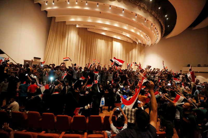 Followers of Iraq's Shi'ite cleric Moqtada al-Sadr are seen in the parliament building as they storm Baghdad's Green Zone after lawmakers failed to convene for a vote on overhauling the government, in Iraq, on April 30, 2016. Photo: Ahmed Saad/Reuters