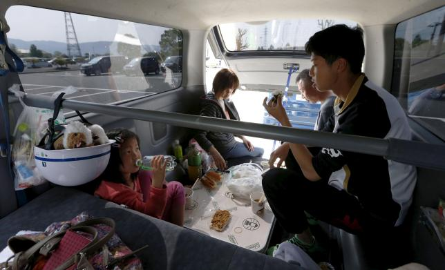 A family of evacuee who have been using their vehicle for shelter rest after a series of earthquakes in Mashiki town, Kumamoto prefecture, southern Japan, in this photo taken by Kyodo April 19, 2016.  Mandatory credit Kyodo/via
