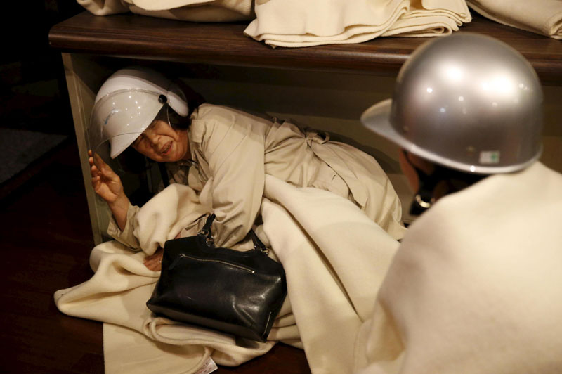 A woman takes shelter after another earthquake hit the area at a hotel in Kumamoto, southern Japan,on Friday, April 16, 2016. Photo: Kyodo/Reuters