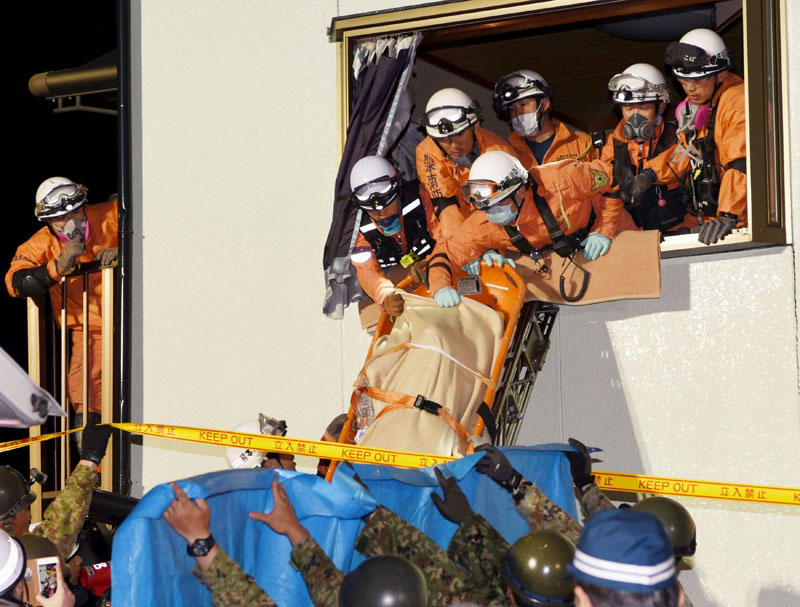 Rescue workers use a stretcher to carry a woman who was rescued from a collapsed house in Mashiki town, Kumamoto prefecture, southern Japan, on Friday, April 15, 2016. Photo Kyodo/Reuters