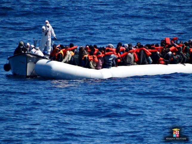 Migrants sit in their boat during a rescue operation of migrants by Italian Navy vessels in this March 18, 2016 handout picture provided by Marina Militare. REUTERS/Marina Militare/Handout via Reuters