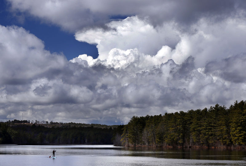 FILE - Storm clouds build prior to the arrival of a thunderstorm as Jeff Warren of Auburn, Maine, heads for shore on his paddleboard on Lower Range Pond, on Thursday, March 17, 2016, in Poland, Maine. Photo: AP