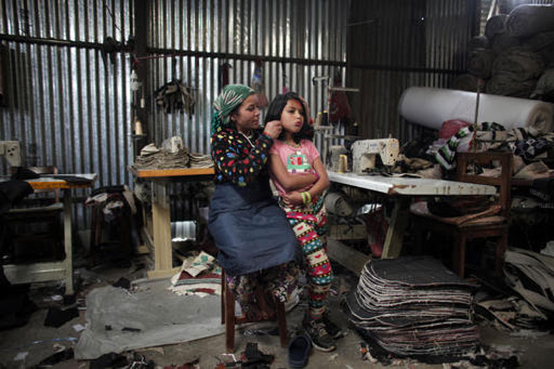 In this March 28, 2016 photo, Maya Pariyar, 39, styles the hair of her daughter Nirmala, 8, at a textile factory in Kathmandu, Nepal. Nirmala, an amputee victim in Nepal's massive 2015 earthquake, has not been in school for a year now, something that deeply worries her parents. The high costs of $1,300 per year for her to go to school in Kathmandu are just unimaginable for her parents. Photo: AP