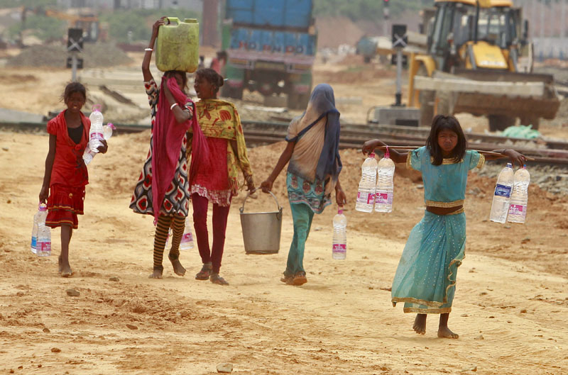 Young girls carry containers filled with drinking water beside the railway station in Agartala, India, on Wednesday, April 20, 2016. Photo: Jayanta Dey/Reuters