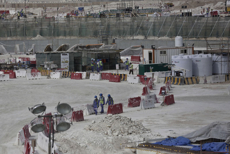 Foreign workers walk between safety barricades at the site of the pitch of the Al-Wakra Stadium that is under construction for the 2022 World Cup in Doha, Qatar, on May 4, 2015. Migrant labourers faced abuse that in some cases amounted to forced labor while working on a stadium that will host soccer matches for the 2022 World Cup in Qatar, a new report released by Amnesty International alleged Thursday, March 31, 2016. Photo: AP
