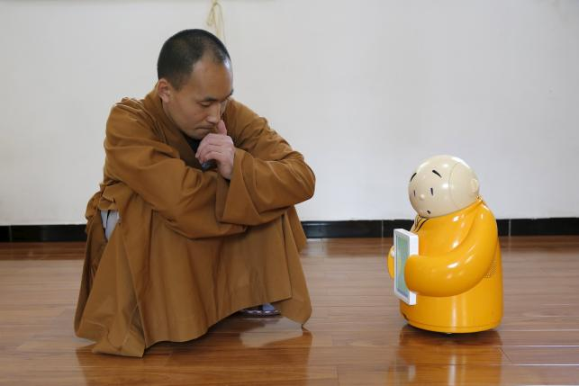 Master Xianfan looks at robot monk Xian'er as he demonstrates the robot's conversation function during a photo opportunity in Longquan Buddhist temple on the outskirts of Beijing, April 20, 2016. REUTERS/Kim Kyung-Hoon