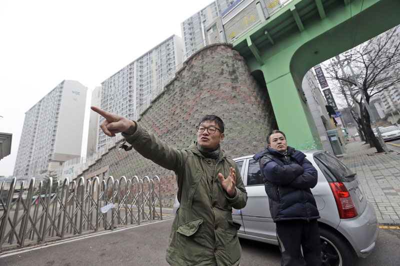 File - Choi Seung-woo (left) and Lee Chae-sik talk as they stand in front of an apartment complex at the former location of the Brothers Home, a mountainside institution where some of the worst human rights atrocities in modern South Korean history took place, in Busan, South Korea, on January 28, 2016. Photo: Ahn Young-joon/AP