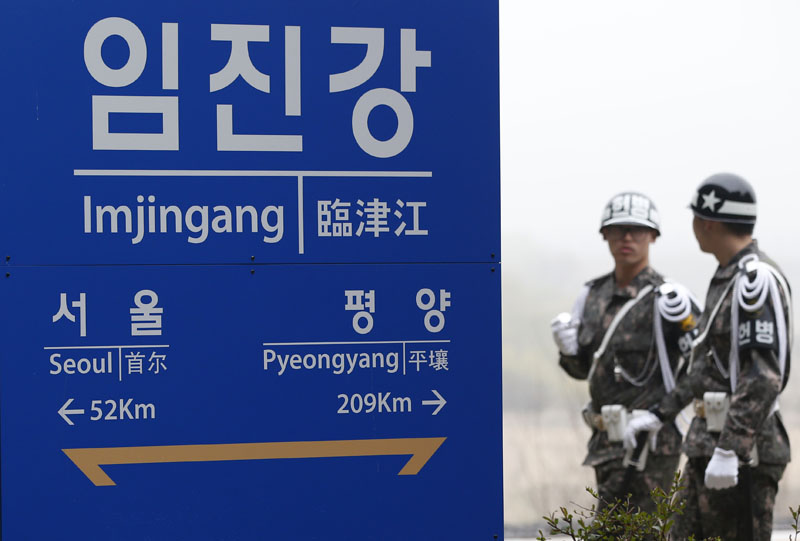 South Korean soldiers walk by a signboard showing the distance to the North Korea's capital Pyongyang and to South Korea's capital Seoul from Imjingang Station near the border village of the Panmunjom in Paju, South Korea, on Saturday, April 9, 2016. Photo: AP