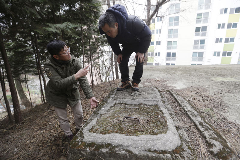 File - Choi Seung-woo (left) and Lee Chae-sik talk as they examine what they say was a water tank left from the Brothers Home, a mountainside institution where some of the worst human rights atrocities in modern South Korean history took place, in Busan, South Korea, on January 28, 2016. Photo: Ahn Young-joon/AP