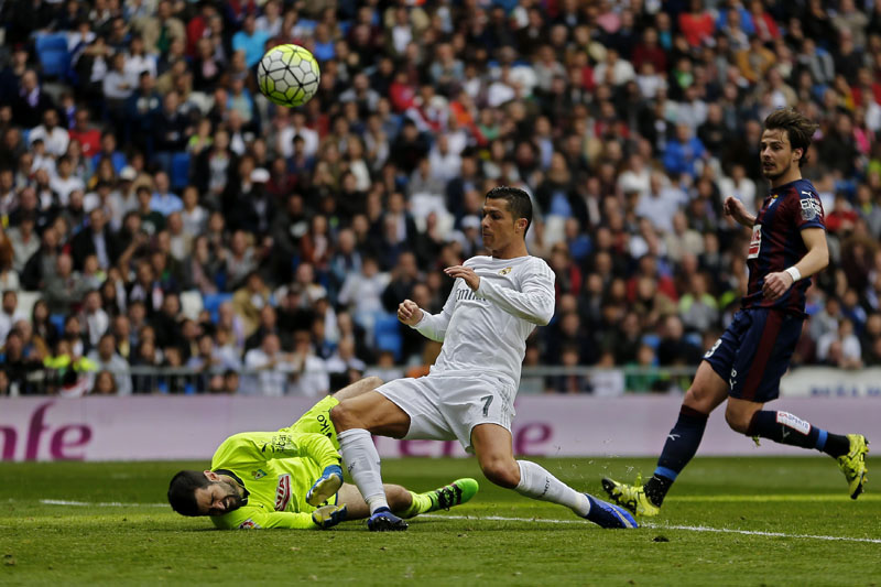 Real Madrid's Cristiano Ronaldo (centre) challenges Eibar's goalkeeper Asier Riesgo (left) during the Spanish La Liga soccer match between Real Madrid and Eibar at the Santiago Bernabeu stadium in Madrid, on Saturday, April 9, 2016. Photo: AP