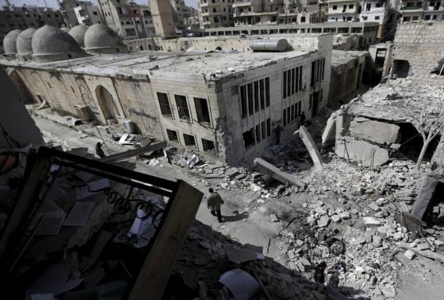 People inspect the damage after a car bomb exploded and targeted a religious center in the rebel-controlled area of Maaret al-Numan town in Idlib province, Syria April 5, 2016. REUTERS/Khalil Ashawi
