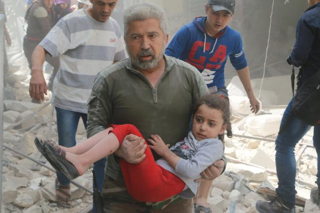 A man carries an injured girl after an airstrike in the rebel held area of old Aleppo, Syria April 22, 2016. REUTERS/Abdalrhman Ismail