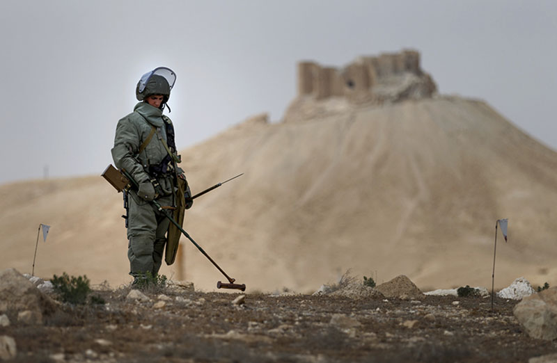 A Russian serviceman checks for mines in Palmyra, Syria, on  Friday, April 8, 2016. Photo: Russian Defence Ministry Press Service Photo via AP