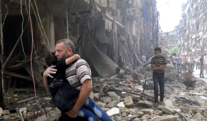 A man carries a child after airstrikes hit Aleppo, Syria, on Thursday, April 28, 2016. Photo: Validated UGC via AP video