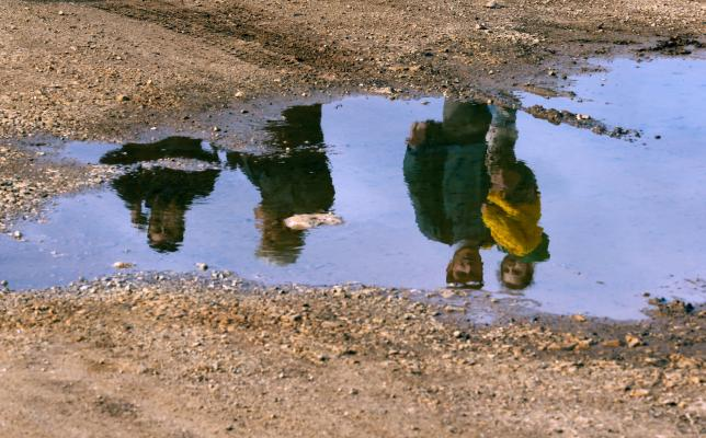 Syrian refugees are reflected in a puddle as they wait on a roadside after Turkish police prevented them from sailing off to the Greek island of Farmakonisi by dinghies, near a beach in the western Turkish coastal town of Didim, Turkey March 9, 2016. REUTERS/Umit Bektas