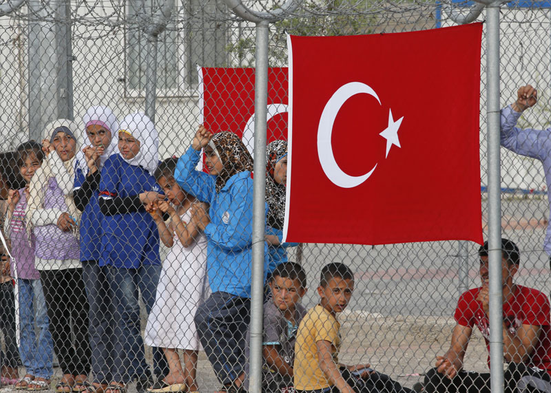 Migrants stand behind a fence at the Nizip refugee camp in Gaziantep province, southeastern Turkey, Saturday, April 23, 2016. Photo: Lefteris Pitarakis/AP