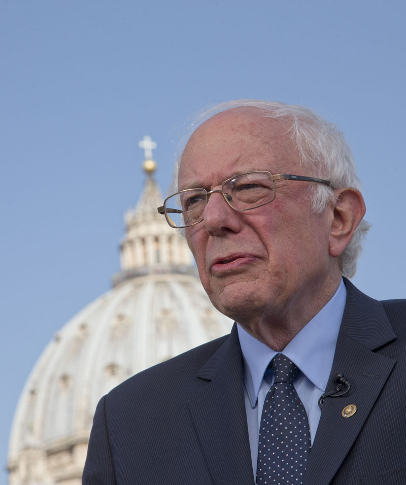 US presidential candidate Bernie Sanders, backdropped by the dome of St. Peter's Basilica, listens to questions during an interview with the Associated Press, at the Vatican, on Saturday, April 16, 2016. Photo: Alessandra Tarantino/AP