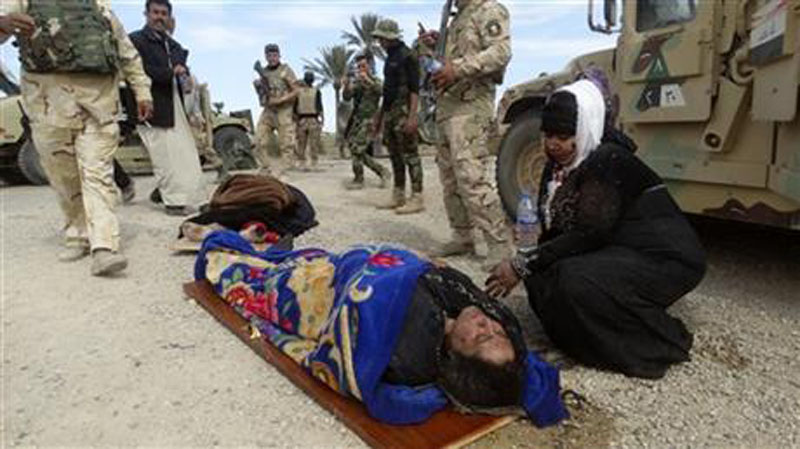 In this Wednesday, March 9, 2016 file photo, an injured woman comforts another as they wait for treatment after clashes between Iraqi Security forces and Islamic State group extremists in a village outside Ramadi, 70 miles (115 kilometers) west of Baghdad. Photo: AP