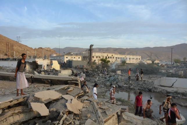 People inspect damage at a site hit by Saudi-led air strikes in the al Qaeda-held port of Mukalla city in southern Yemen April 24, 2016.  REUTERS/Stringer