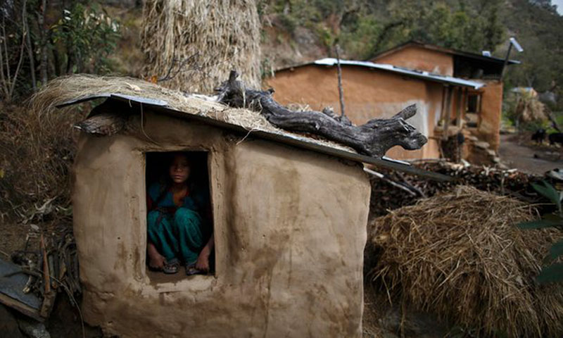 A young woman sits inside a Chhaupadi shed in the hills of Legudsen village in Achham in western Nepal. Photo: The Guardian