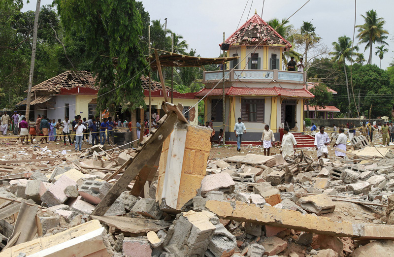 People stand next to debris after a broke out at a temple in Kollam in the southern state of Kerala, India, April 10, 2016. Photo: Reuters