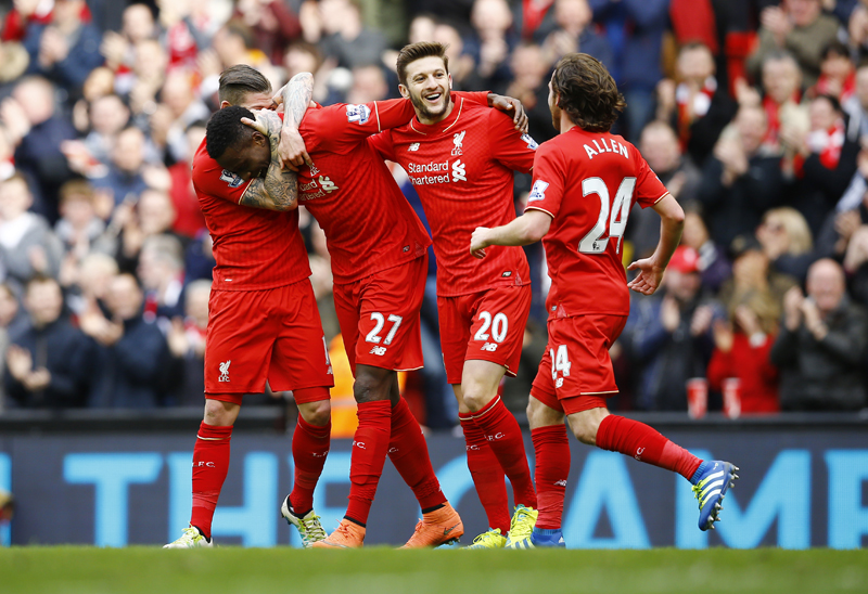 Divock Origi celebrates scoring the fourth goal for Liverpool with Adam Lallana and teammates against Stoke City during Barclays Premier League at Anfied on Sunday, April 10, 2016. Photo: Reuters