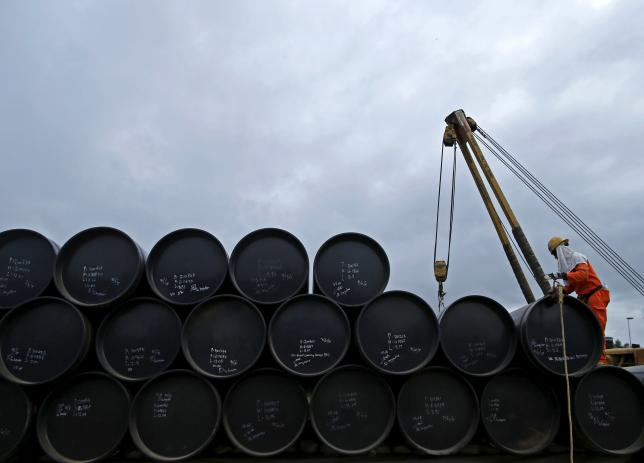 A worker prepares to transport oil pipelines to be laid for the Pengerang Gas Pipeline Project at an area 40km (24 miles) away from the Pengerang Integrated Petroleum Complex in Pengerang, Johor, February 4, 2015.  REUTERS/Edgar Su/Files