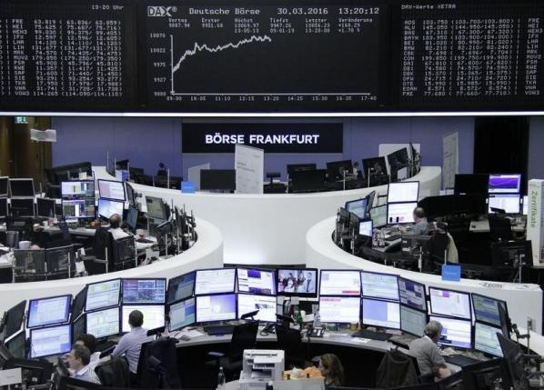 Traders work at their desks in front of the German share price index, DAX board, at the stock exchange in Frankfurt, Germany, March 30, 2016. REUTERS/Staff/Remote