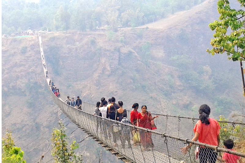 Visitors cross the tallest suspension bridge of Nepal above the Modi river in Parbat district on Wednesday, April 13, 2016. Photo: RSS