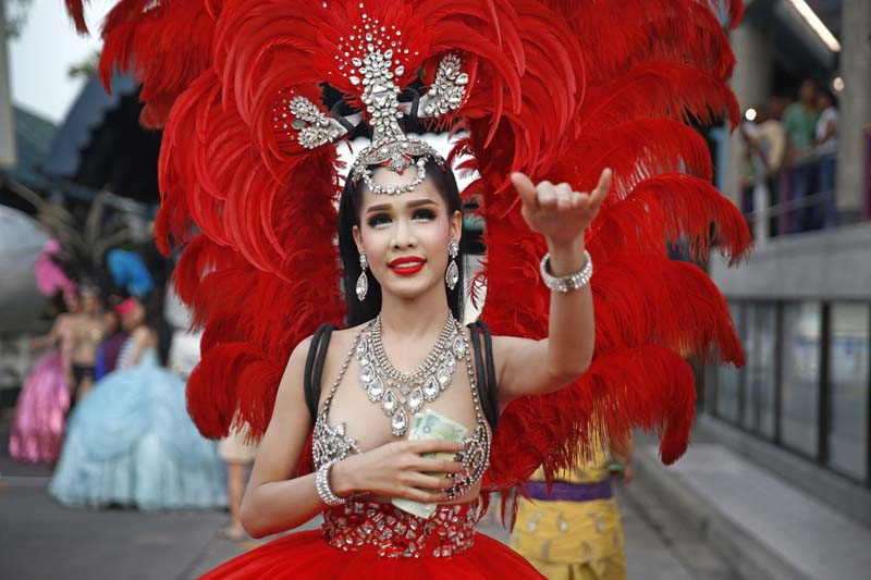 A Lady boy dressed in extravagant costume collects money to take photos with them before a cultural dance at Alcazar Cabaret Show in Pattaya, Thailand on Sunday, May 22, 2016. Photo: Skanda Gautam/ THT