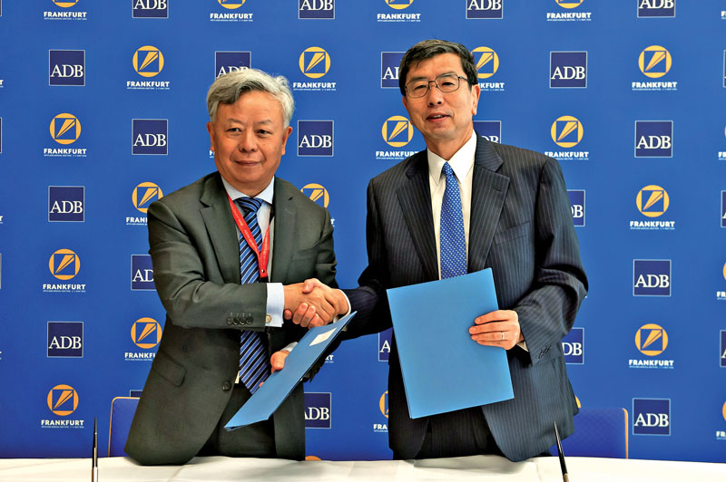 ADB President Takehiko Nakao (right) and AIIB President Liqun Jin shaking hands after signing an MoU to strengthen cooperation for sustainable growth, in Frankfurt, on Monday, May 2, 2016. Photo: THT