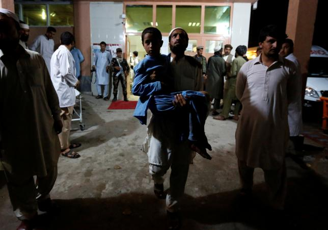 An Afghan man carries a slightly wounded boy after a blast, at a hospital in Jalalabad, Afghanistan, May 10, 2016. REUTERS/Parwiz