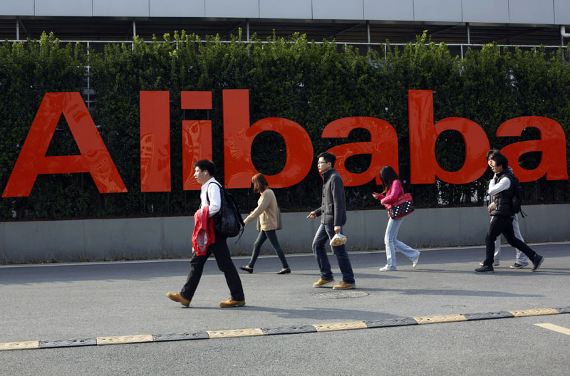 People walk past a company logo at the Alibaba Group headquarters in Hangzhou, in eastern China's Zhejiang province, on March 17, 2014. Photo: Chinatopix via Ap