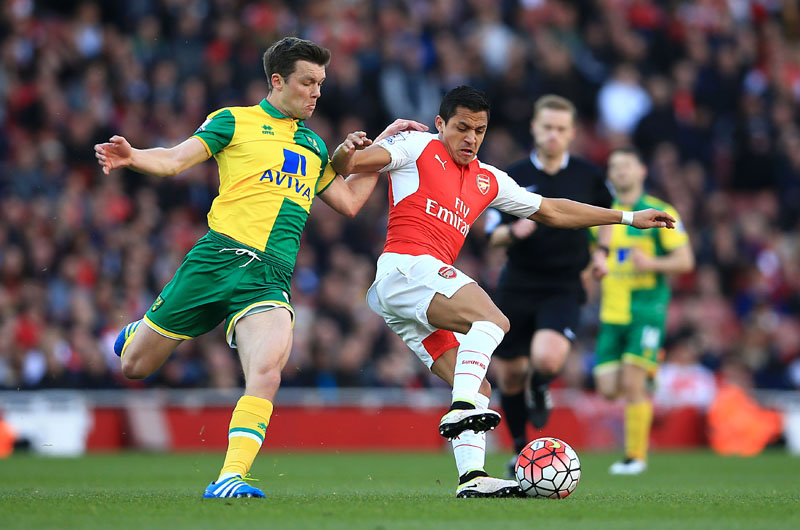 Norwich City's Jonny Howson, left and Arsenal's Alexis Sanchez battle for the ball, during the English Premier League soccer match between Arsenal and Norwich City, at the Emirates Stadium, in London, Saturday April 30, 2016. ( John Walton/PA via AP) UNITED KINGDOM OUT NO SALES NO ARCHIVE