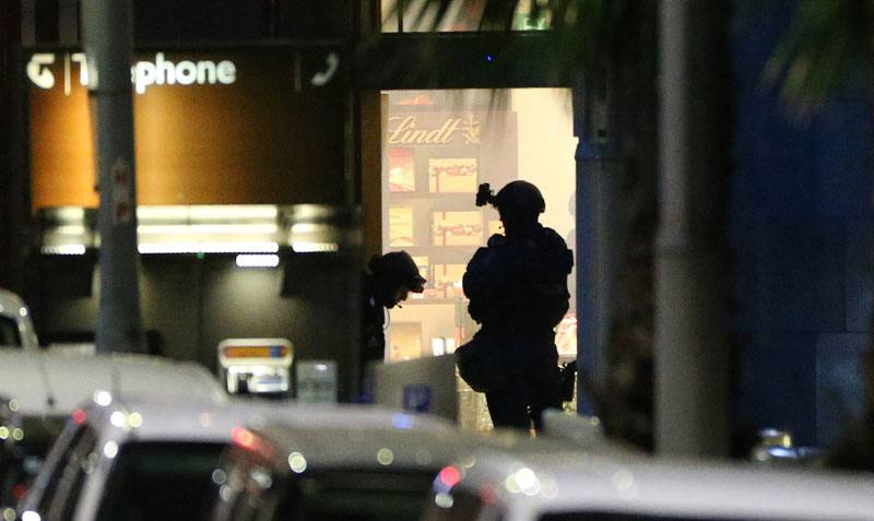 FILE u2013 Armed tactical response officers stand ready to enter the Lindt cafe during a siege in the central business district of Sydney, Australia, on December 16, 2014. Photo: Glenn Nicholls/AP File