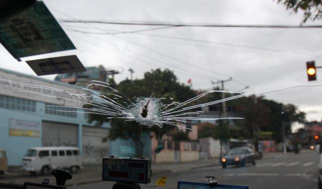 The window of a taxi is hit by a bullet as Reuters' photographer Paulo Whitaker was injured during an operation at Vila Cruzeiro slum in Rio de Janeiro November 26, 2010. REUTERS/Paulo Whitaker/Files