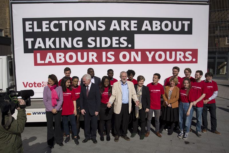 Jeremy Corbyn (centre), the leader of Britain's opposition Labour party, poses for a group photograph with party members after unveiling a local council election campaign poster in London, on Tuesday, May 3, 2016.  A local council election takes place across England on Thursday. Photo: Matt Dunham/AP