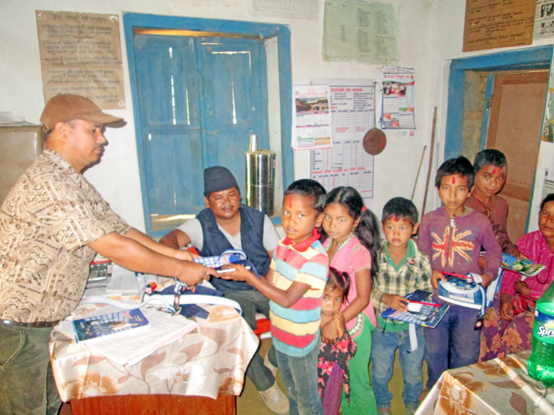 A Principal, at a local primary school in Byas Municipality, welcomes children, with vermilion, books, copies and pen, on Tuesday, May 10. Children's parents work as laborer in local brick kiln. Photo: Madan Wagle