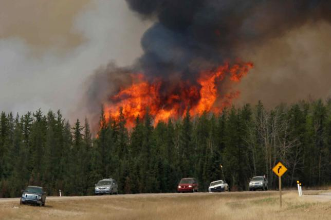 A wildfire burns as evacuees who were stranded north of Fort McMurray, Alberta, Canada head south of Fort McMurray on Highway 63, May 6, 2016. REUTERS/Chris Wattie/File Photo