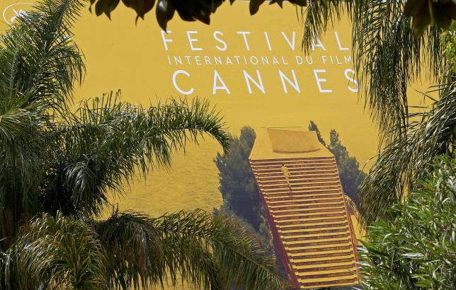 Palm fronds and trees frame a giant canvas of the official poster of the 69th Cannes Film Festival in Cannes, France, May 9, 2016.  REUTERS/Yves Herman