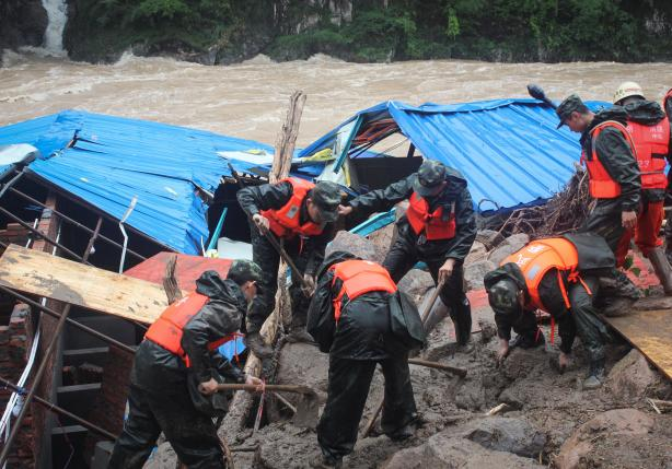 Paramilitary policemen search for missing people at the site of a landslide in Sanming, Fujian province, China, May 8, 2016. China Daily/via REUTERS A