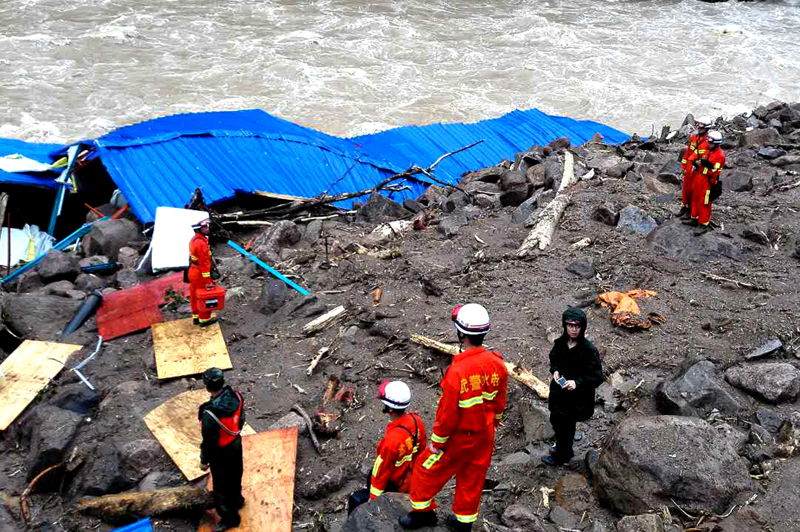 Rescuers look at a damaged building as they search for potential survivors at the site following a landslide in Taining county in southeast China's Fujian province, Sunday, May 8, 2016. Photo: AP