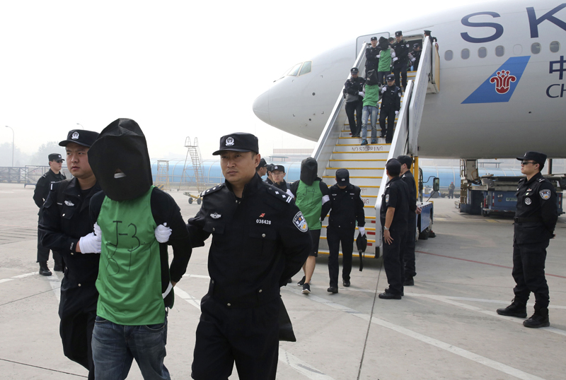In this April 13, 2016 file photo released by Xinhua News Agency, Chinese suspects involved in wire fraud are escorted off a plane upon arriving at the Beijing Capital International Airport in Beijing, China. Photo: Xinhua/AP