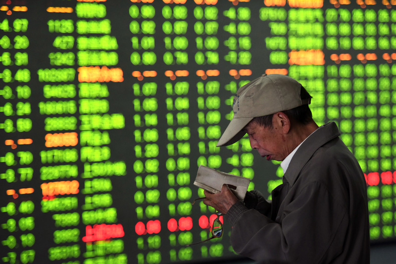 A Chinese investor checks his notes while monitoring stock prices at a brokerage house in Hangzhou in eastern China's Zhejiang province Friday, May 6, 2016. Photo: AP