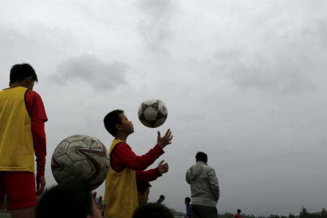 Students warm up before training session at Evergrande soccer academy in Qingyuan, southern China December 4, 2015. Photo: Reuters