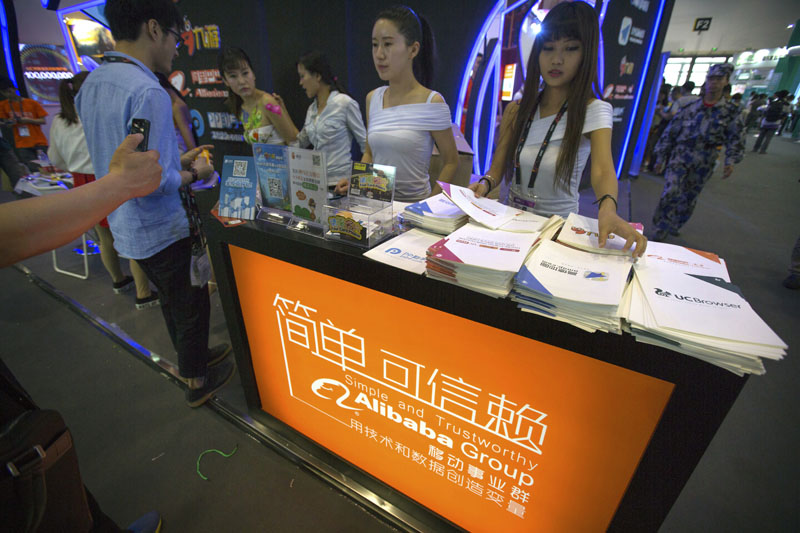Staff members hand out brochures to visitors at the Alibaba booth at the Global Mobile Internet Conference in Beijing, on April 29, 2015. Photo: Mark Schiefelbein/AP