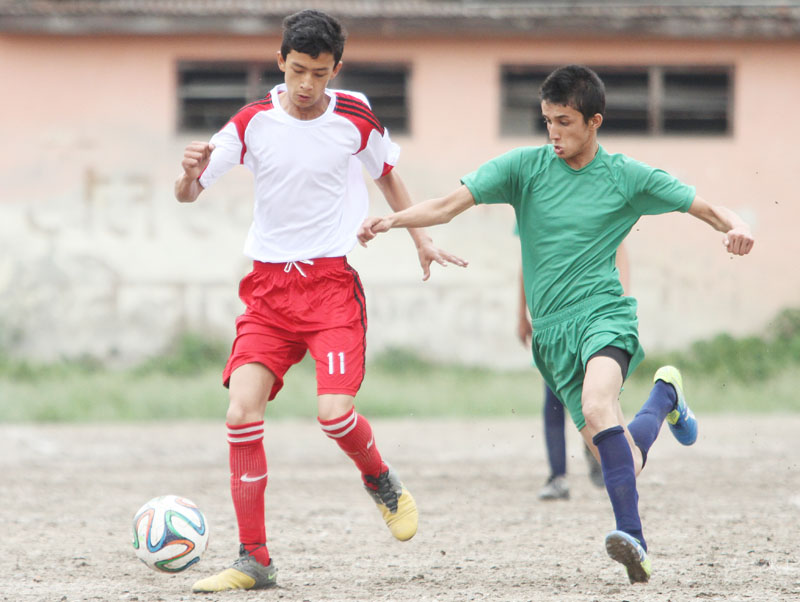 Players of Apple International and Mandala International (right) vie for the ball during their Coca-Cola Cup Inter-school Football Tournament match in Kathmandu on Wednesday, May 25, 2016. Photo: THT